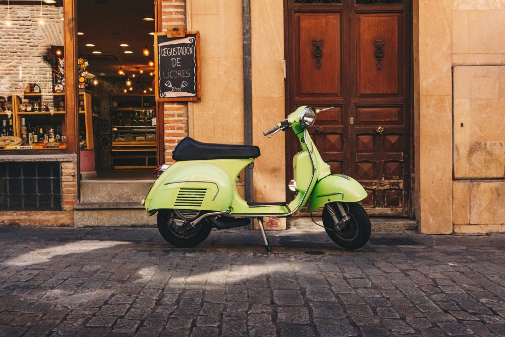 Green scooter in front of restaurant on cobblestone street